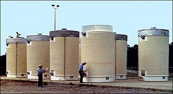image of Storage and Transportation of Spent Nuclear Fuel with two workers inspecting of an array of spent fuel storage containers