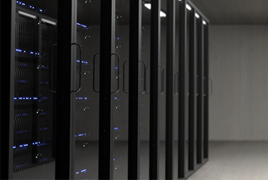 Image of computer server room with twelve large tall black servers with small blue lights sitting on a grey floor.