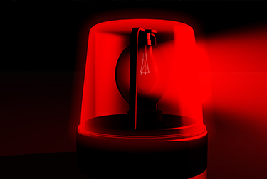 Image of a red emergency light on a black background.
