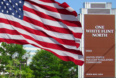 Image of the Nuclear Regulatory Commission's outdoor building signage at their headquarters in Maryland with an American Flag flying next to it.