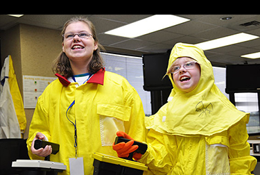 Image of two your girls in yellow protective coats holding remote controls.
