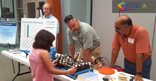 NRC Region III staff members talk with a young member of the community during the annual assessment event for DC Cook nuclear plant in Michigan.