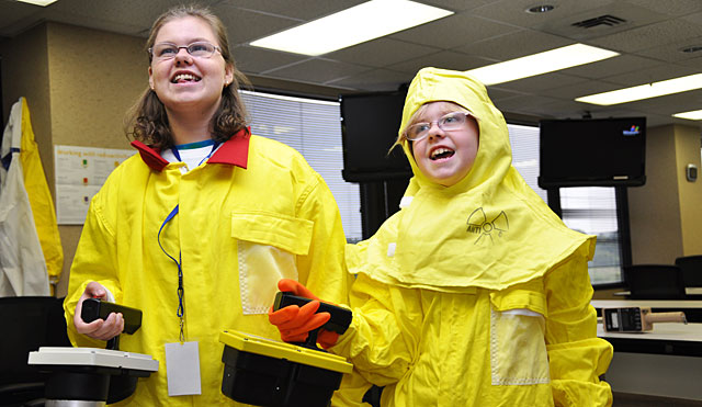 Two female students dressed in safety gear holding Geiger-Mueller counters