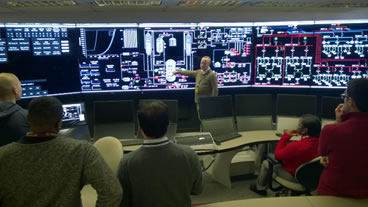 images of a person pointing to displays that have reactors digital diagrams and people facing and listening to person in the middle