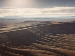 Aerial view of Yucca Mountain, looking northwest, showing the desert environment. The proposed geologic repository would be located about 300 meters (1,000 feet) below the eastern slope of the mountain.