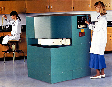 photo of two women in a lab environment with one operating a gamma irradiator